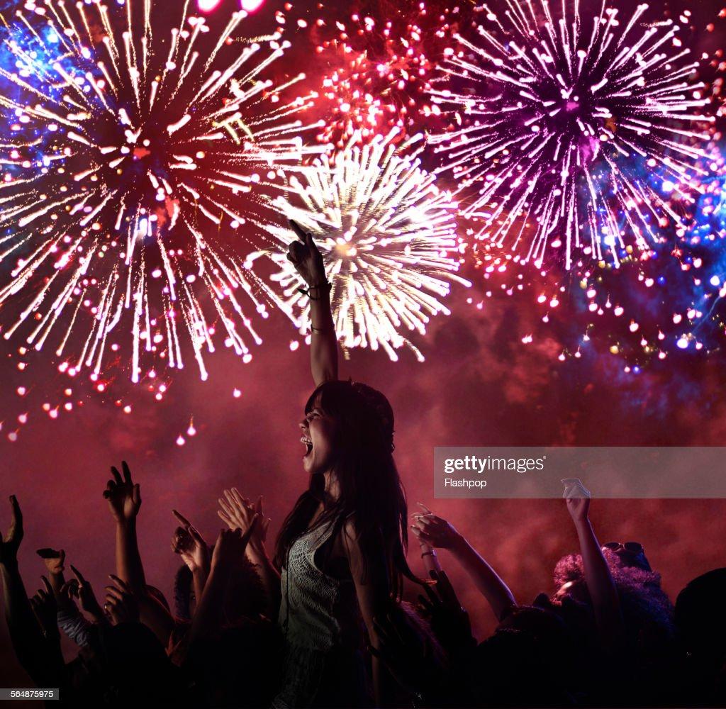 Woman amongst crowd enjoying firework display : Stock Photo