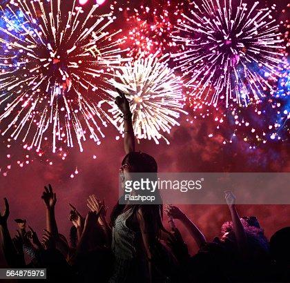 Woman amongst crowd enjoying firework display