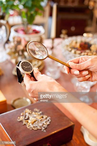 Woman analysing watch at flea market