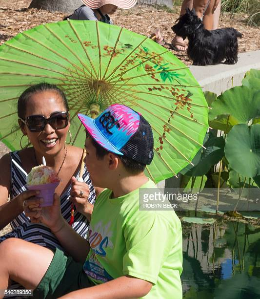 A woman and a boy enjoy a shaved ice treat during the 36th annual Lotus Festival which celebrates the annual lotus blooms and the contributions of...