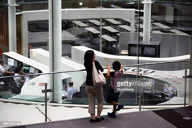A woman and a boy look at the trading floor of the Tokyo Stock Exchange operated by Japan Exchange Group Inc in Tokyo Japan on Tuesday Aug 25 2015...