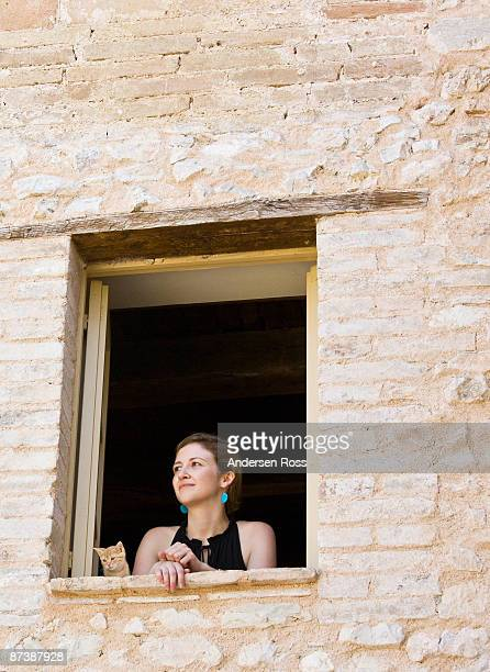 Woman and a cat looking out a window