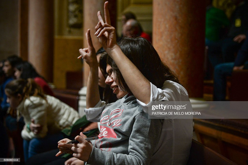 A woman and a child celebrate after the majority of deputies voted in favour of a law authorizing adoption by homosexual couples at the Portuguese parliament in Lisbon on February 10, 2016. Last January President Cavaco Silva vetoed this law but had his hand forced today with the majority of the parliament voting for the adoption of the law. / AFP / PATRICIA DE MELO MOREIRA