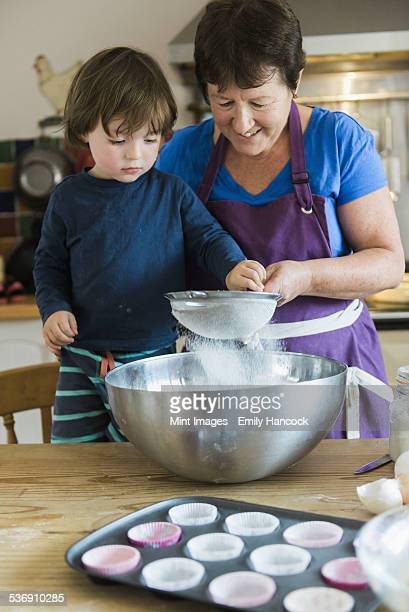 A woman and a child cooking at a kitchen table, making fairy cakes.