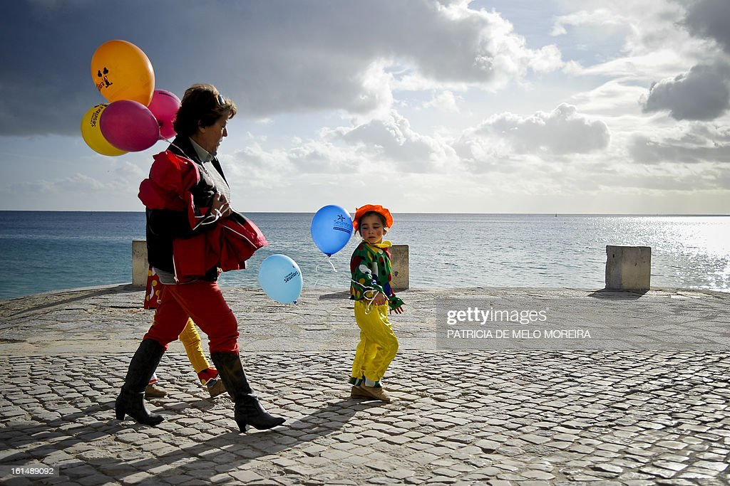 A woman and a child dressed as clowns and carrying balloons walk in front of the beach during a clown parade in Sesimbra, on February 11, 2013.