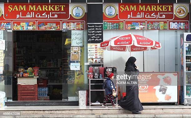 A woman and a child leave a Syrian shop in Mersin south of Turkey on March 12 2015 where at least 200000 Syrians live after feeing the war in their...