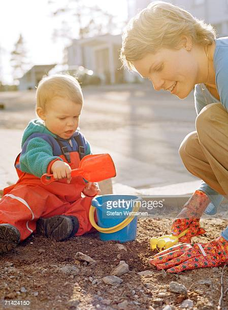 A woman and a child playing in a sandpit.