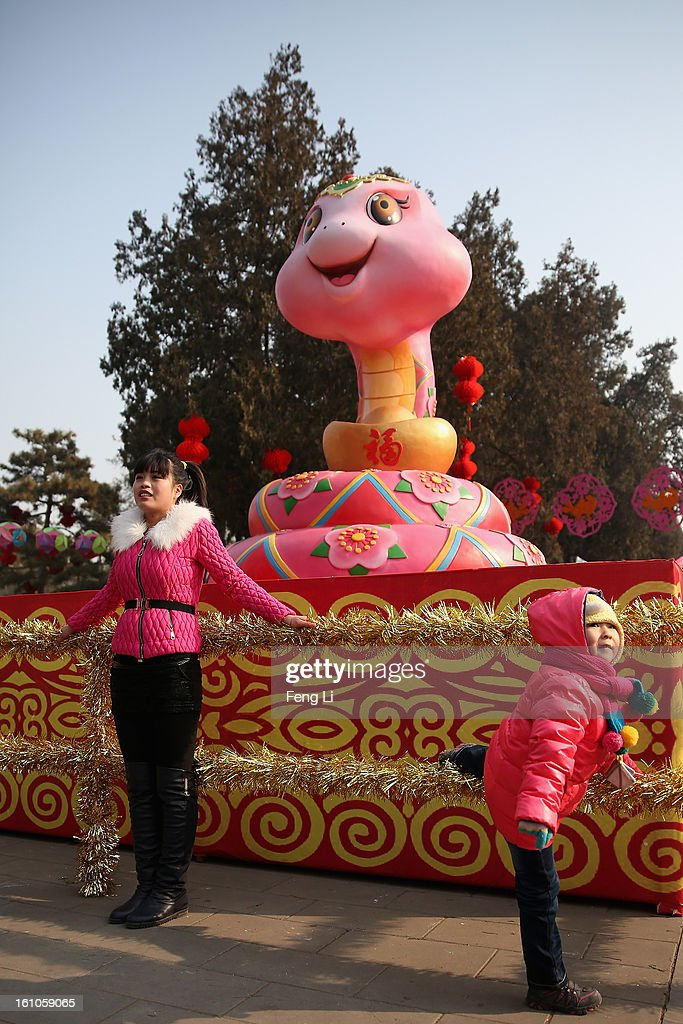 A woman and a child pose for photo next to a snake sculpture at the Spring Festival Temple Fair for celebrating Chinese Lunar New Year of Snake at the Temple of Earth park on February 9, 2013 in Beijing, China. The Chinese Lunar New Year of Snake also known as the Spring Festival, which is based on the Lunisolar Chinese calendar, is celebrated from the first day of the first month of the lunar year and ends with Lantern Festival on the Fifteenth day.