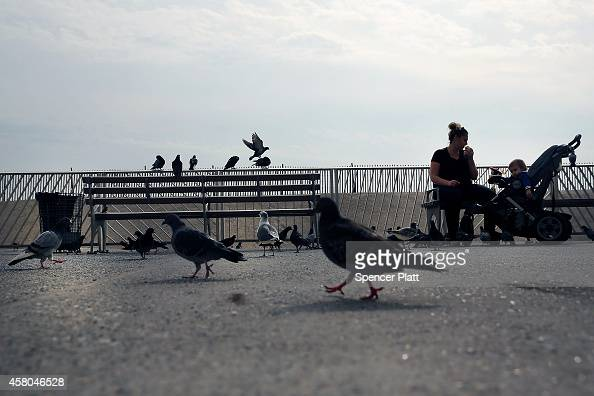A woman and a child relax along a recently repaired section of boardwalk at Rockaway Beach which was heavily damaged during Hurricane Sandy on...