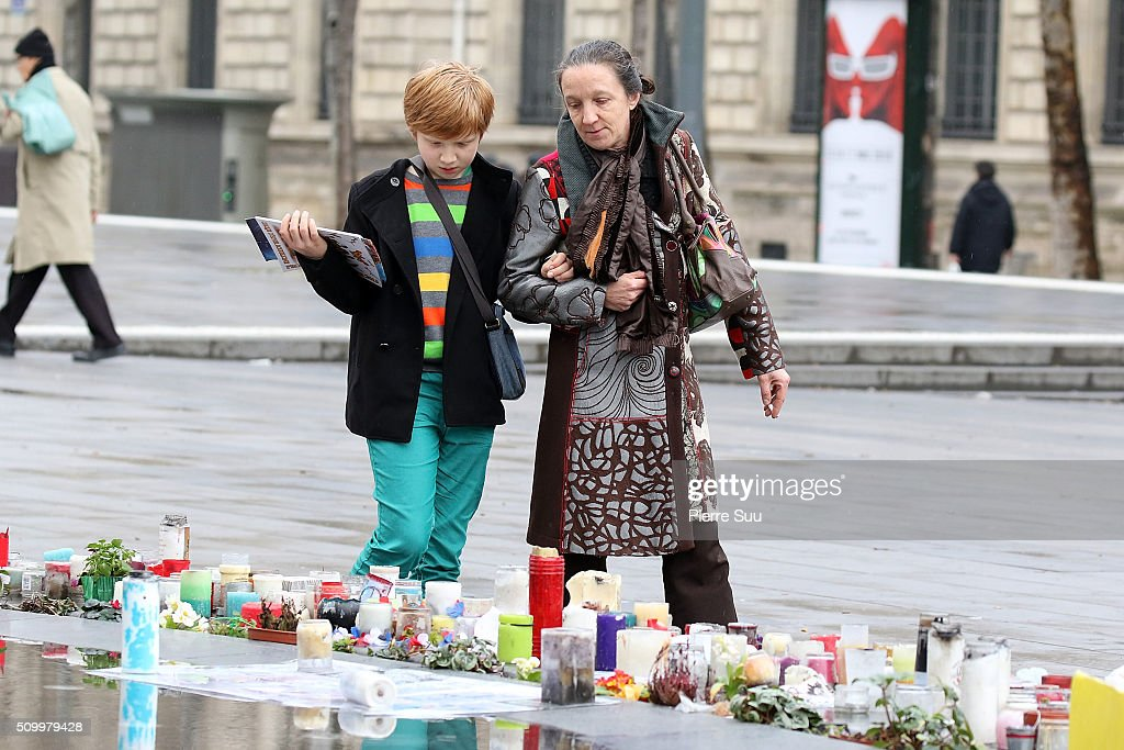 A woman and a child stand in front of the monument at the Republique square on February 13, 2016 in Paris, France.People continue to leave tributes to victims three months after the Paris terrorist attacks.