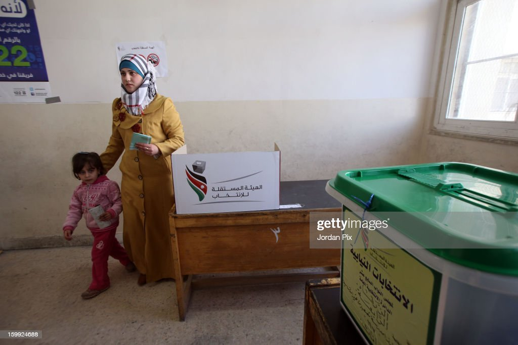 A woman and a child stand near a cardboard votring booth as Jordanians vote in the parliamentary elections on January 23, 2013 in the city of Zarqa, Jordan. Jordan's election is being boycotted by the Muslim Brotherhood's political wing, the Islamic Action Front (IAF), who claim that the system is rigged favorably to supporters of the king, who for the first time will appoint the new prime minister.