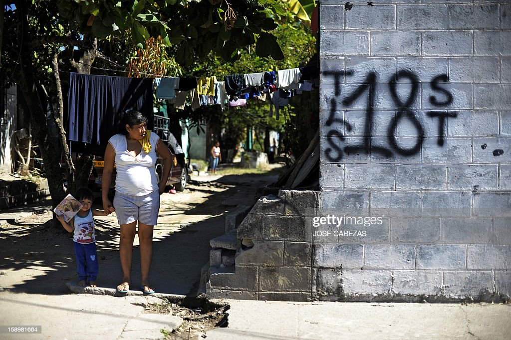 A woman and a child stand next to a graffiti of the 'Mara 18' gang before it is erased at Valle del Sol neighborhood in Apopa, 14 km north of San Salvador, El Salvador on January 4, 2013. Raul Mijango, Gang truce mediator, announced that 18 districs in El Salvador will be considered 'Sanctuary Territories' for gangs as a second stage of the gang truce. AFP PHOTO/ Jose CABEZAS