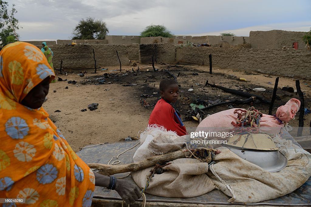 A woman and a child stand next to their house destroyed by a French airstrike on January 27, 2013 in Lere. French-led forces on Janaury 28, 2012 seized Mali's fabled desert city of Timbuktu in a lightning advance north as fleeing Islamists torched a building housing priceless ancient manuscripts. AFP/PHOTO ERIC FEFERBERG