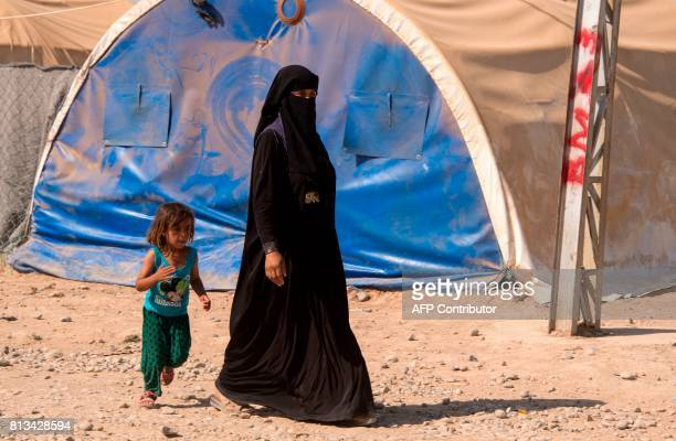 A woman and a child walk in a UNHCR refugee camp in Hammam alAlil on the outskirts of Mosul on July 12 2017 Iraqi Prime Minister Haidar AlAbadi...