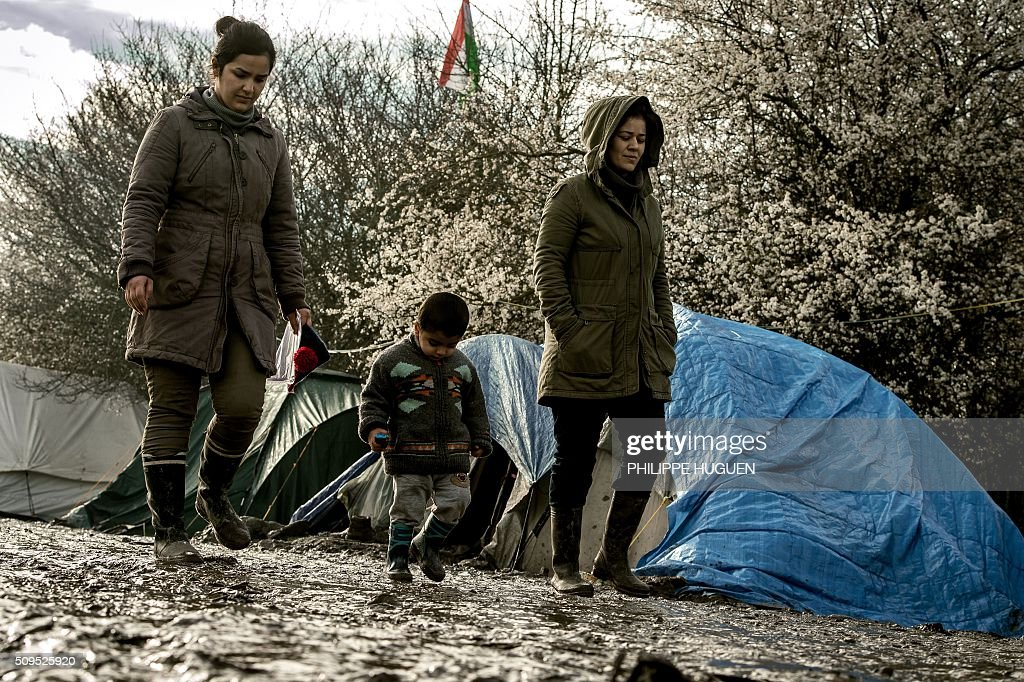 Woman and a child walk in the so-called 'Jungle' migrant camp in Gande-Synthe where 2,500 refugees from Kurdistan, Iraq and Syria live on February 11, 2016 in Grande-Synthe near the city of Dunkirk, northern France. / AFP / PHILIPPE HUGUEN