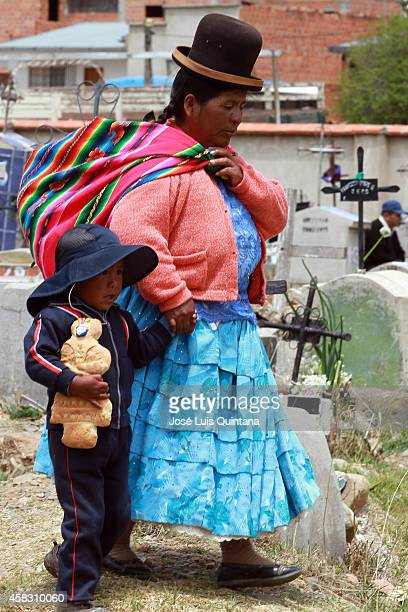A woman and a child walk on the cemetery during the celebration of 'All Saints' of Aymara Indians at Héroes del Gas Sur cemetery on November 02 La...