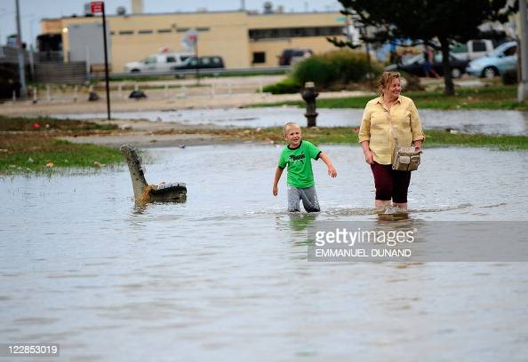 A woman and a child walk through floodwater on Rockway Beach after Hurricane Irene swept through the city in New York August 28 2011 AFP...