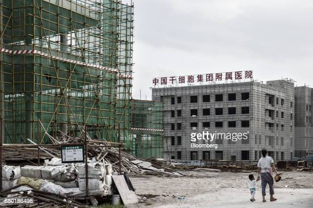 A woman and a child walk through the construction site of a China Stem Cell Group hospital inside the Hainan Boao Lecheng...
