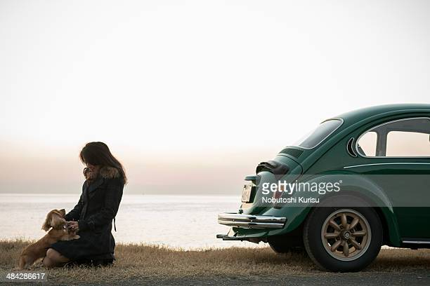A woman and a dog are standing near the car