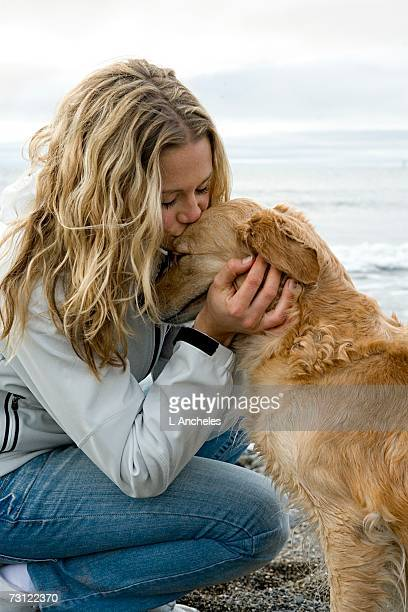 A woman and a dog on the beach.