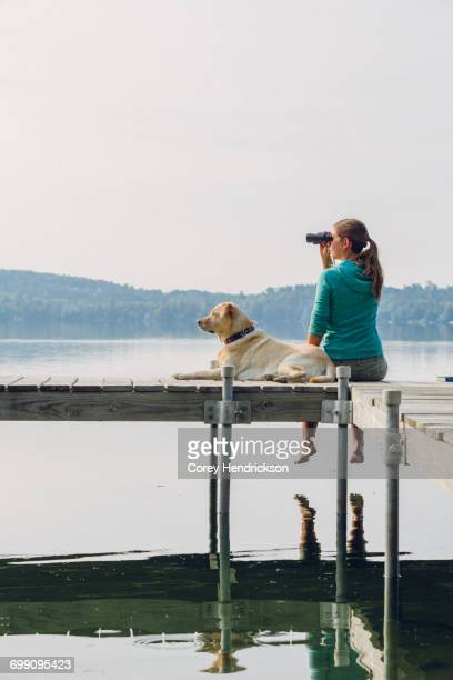 Woman and a dog sitting on a lake dock.