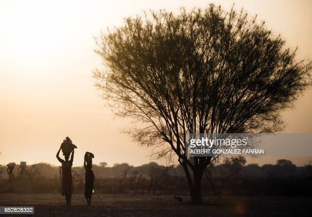 TOPSHOT A woman and a girl carry food from a distribution centre in Ngop in South Sudan's Unity State on March 10 2017 The Norwegian Refugee Council...
