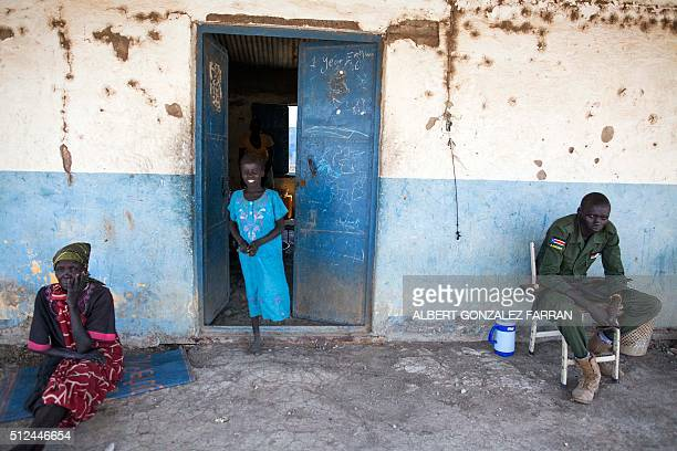 A woman and a girl from the Dinka community are pictured next to a soldier in the Sobat Secondary School in Malakal on February 26 2016 The Dinka...