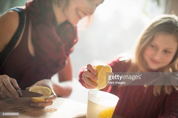 A woman and a girl sitting at a table, girl squeezing the juice from a lemon into a glass.