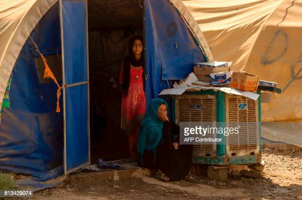 A woman and a girl walk in a UNHCR refugee camp in Hammam alAlil on the outskirts of Mosul on July 12 2017 Iraqi Prime Minister Haidar AlAbadi...