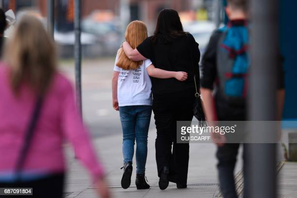TOPSHOT A woman and a girl wearing a tshirt of US singer Ariana Grande leave a hotel near the Manchester Arena following a deadly terror attack in...