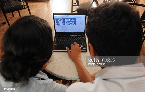 A woman and a man look at a Facebook page in Agadir on October 11 published in support of the three Moroccan teenagers arrested for posting Facebook...