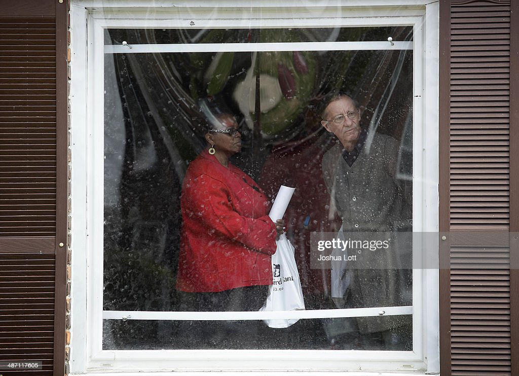A woman and a man look out of a window as they tour one of twelve homes being auctioned off in the East English Village neighborhood April 27, 2014 in Detroit, Michigan. The city of Detroit and the Detroit Land Bank will auction off 12 homes starting May 5. One home will be auctioned off per day with an opening bid of $1,000.