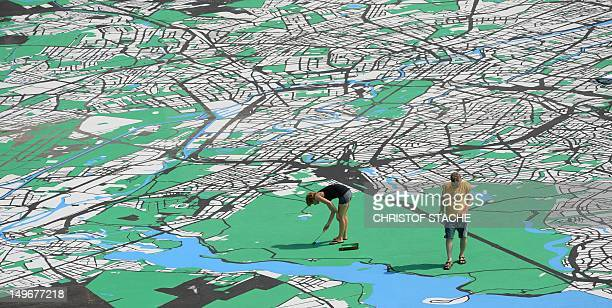 A woman and a man paint a detail of a city map of Berlin on the German capital's Schlossplatz on August 2 2012 The giant map that is scheduled to be...