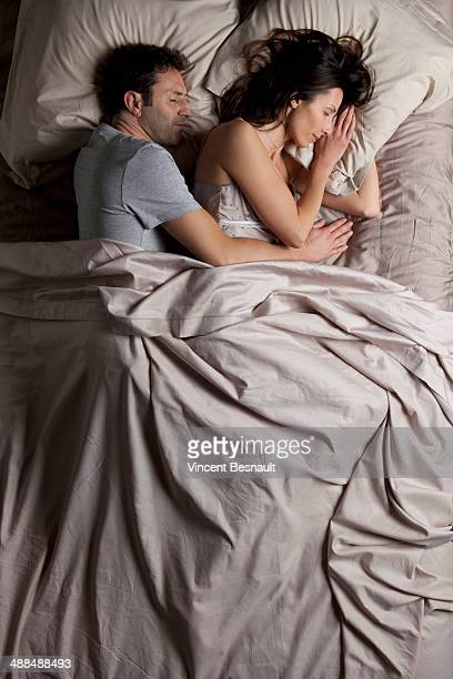 Woman and a man sleeping in bed