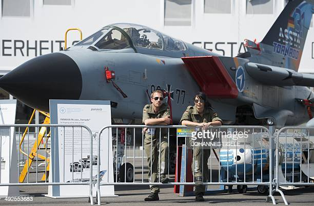 A woman and a man stand in front of a Tornado combat aircraft of the German armed forces Bundeswehr at the International Air Show ILA in Schoenefeld...