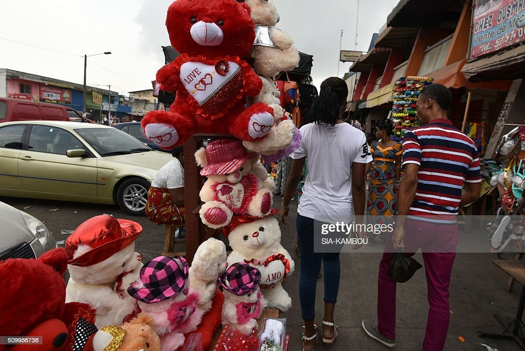 A woman and a man walk near Valentine's day items on February 13, 2016 in a street market in Marcory, a popular suburb of the Ivorian capital. / AFP / SIA-KAMBOU