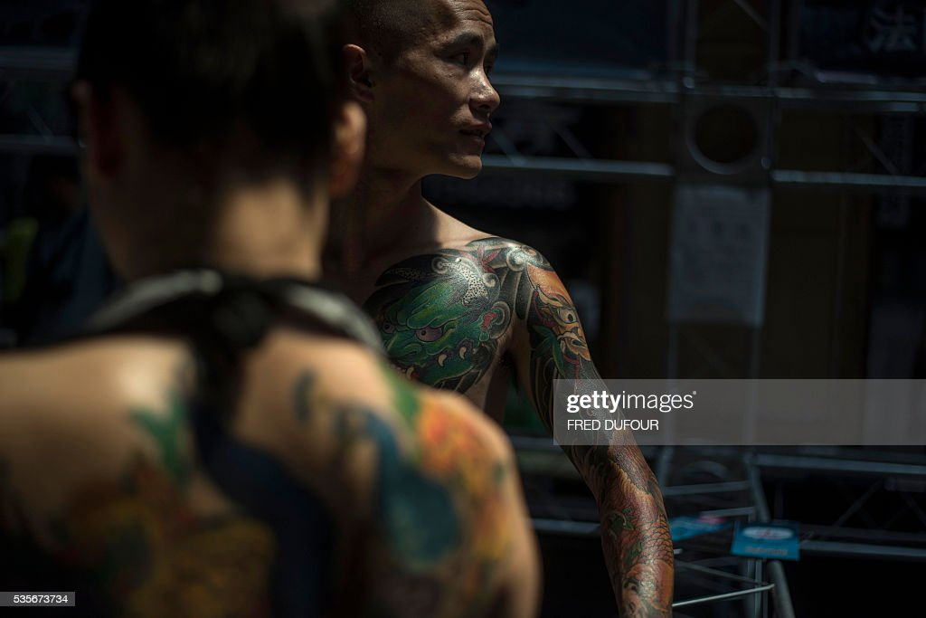 A woman and a man with tattoos attends the Langfang International Tattoo show, in Hebei province, on May 29, 2016. / AFP / FRED