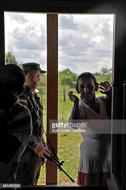 A woman and a police officer look inside the 'House of the Balcony' a bunker of the former paramilitary commander of the United SelfDefense Forces of...