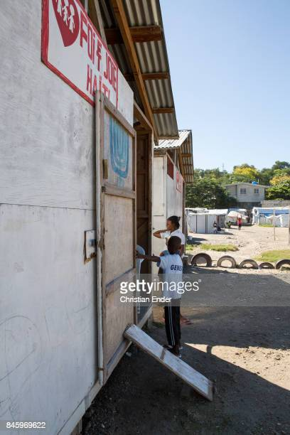 PortauPrince Haiti December 09 2012 A woman and a young boy are standing in front of the entrance of a first aid building in the refugee camp Parc...