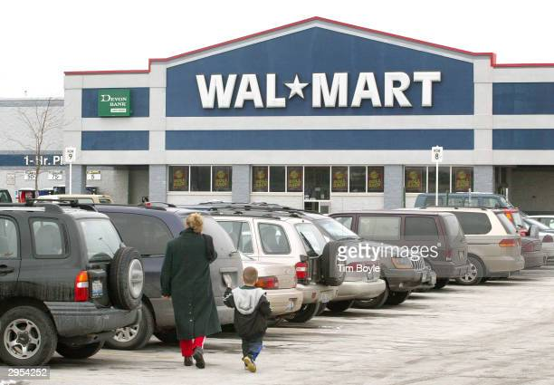 A woman and a young boy walks towards the entrance of a WalMart store February 9 2004 in Niles Illinois WalMart may be entering a deal with Time Inc...
