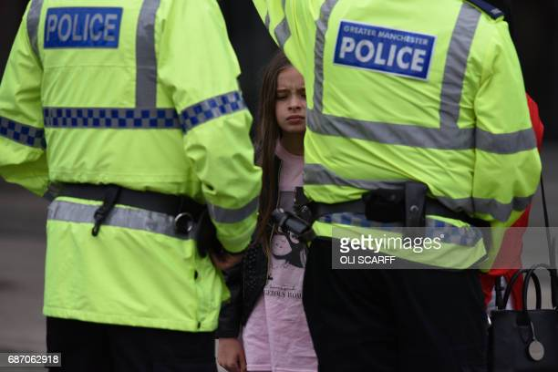 TOPSHOT A woman and a young girl wearing a tshirt of US singer Ariana Grande talks to police near Manchester Arena following a deadly terror attack...