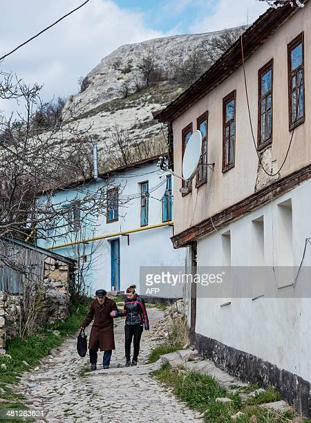 A woman and an old man walk along a street in Bakhchisaray Crimea on March 29 2014 Ethnic Tatars from all over Crimea convened in the town of...