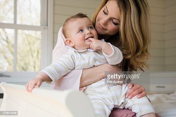 Woman and baby smiling, sitting on the bed