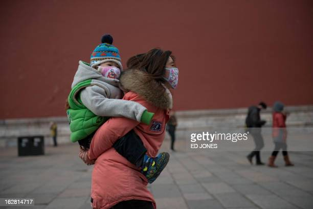 A woman and baby wearing face masks walk in the Forbidden City during heavy pollution in Beijing on February 28 2013 Beijing residents were urged to...