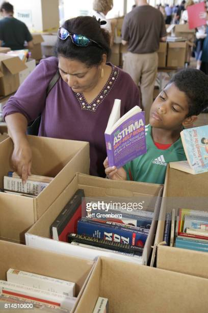 A woman and boy browsing books at the MiamiDade Public Library Book Sale