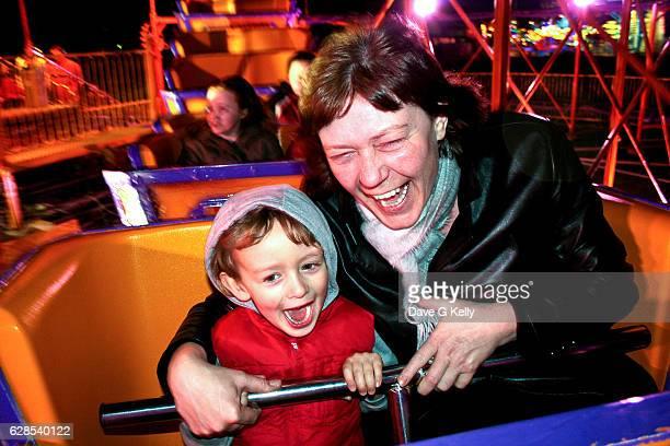 A Woman and Boy Enjoying a Rollercoaster Ride at an Amusement Park.