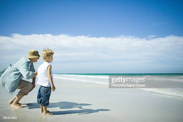 'Woman and boy standing on beach, looking towards waves'