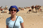 The woman poses on a camels background, Egypt