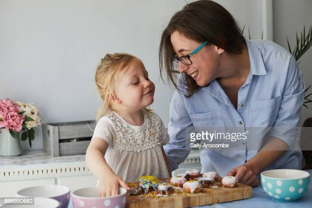 Woman and child decorating doughnuts together