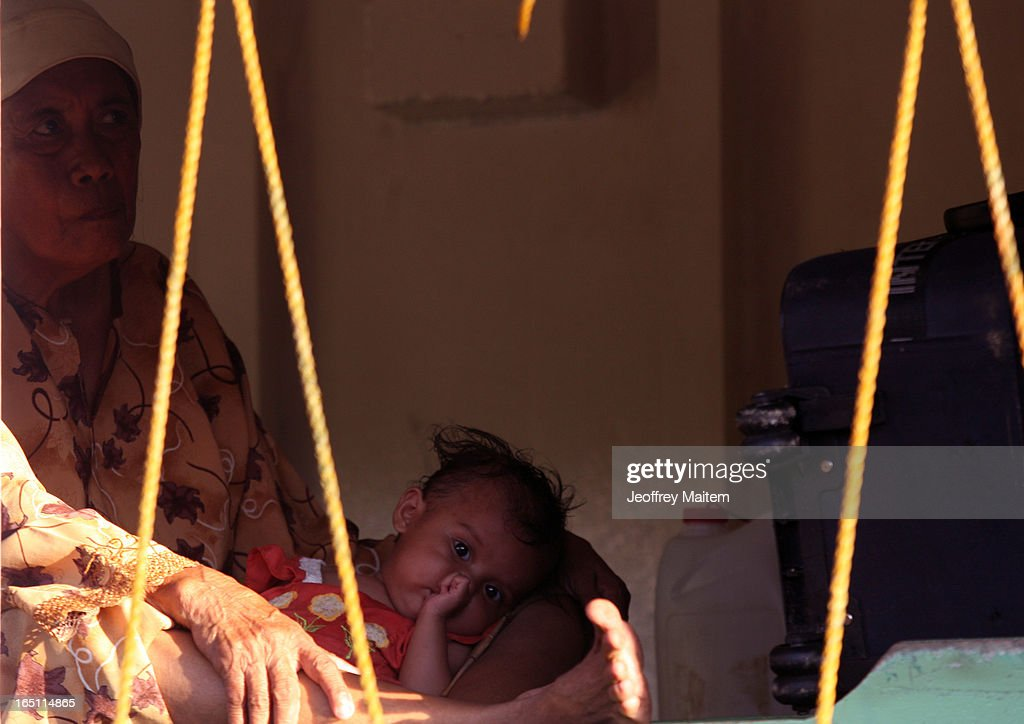 A woman and child displaced by continuing armed conflict between the supporters of Philippine Muslim clan Sulu Sultan Jamalul Kiram III and Royal Malaysian Police in Sabah, Malaysia, sit inside a boat as they arrive at Bonggao on March 30, 2013 in Bonggao, Tawi-Tawi, Philippines. Following the insurgency in Sabah and the Malaysian government's subsequent crackdown on undocumented Filipinos, over 4000 people, mostly Filipino Muslims, have begun evacuating to the southern provinces of Basilan, Sulu, and Tawi-Tawi in the Philippines, with numbers expected to reach more than 100,000.